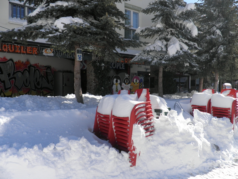 Snow on stacked up red chairs, Sierra Nevada